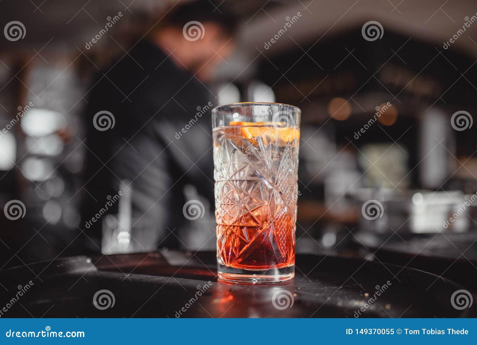 C?cteles en una barra del c?ctel con anaranjado y rojo