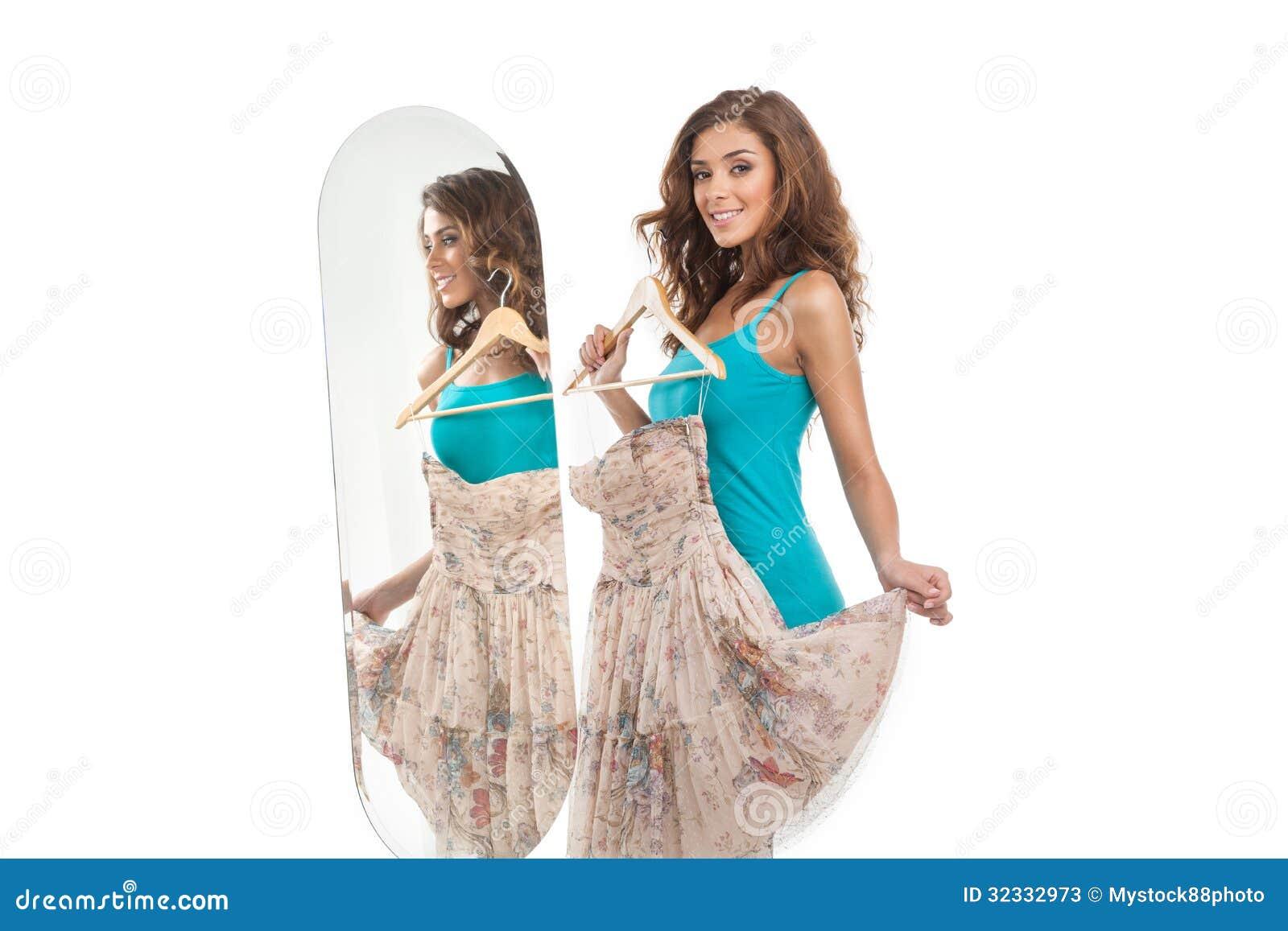 ¿Cómo estoy mirando? Mujeres jovenes hermosas que sostienen un vestido mientras que st