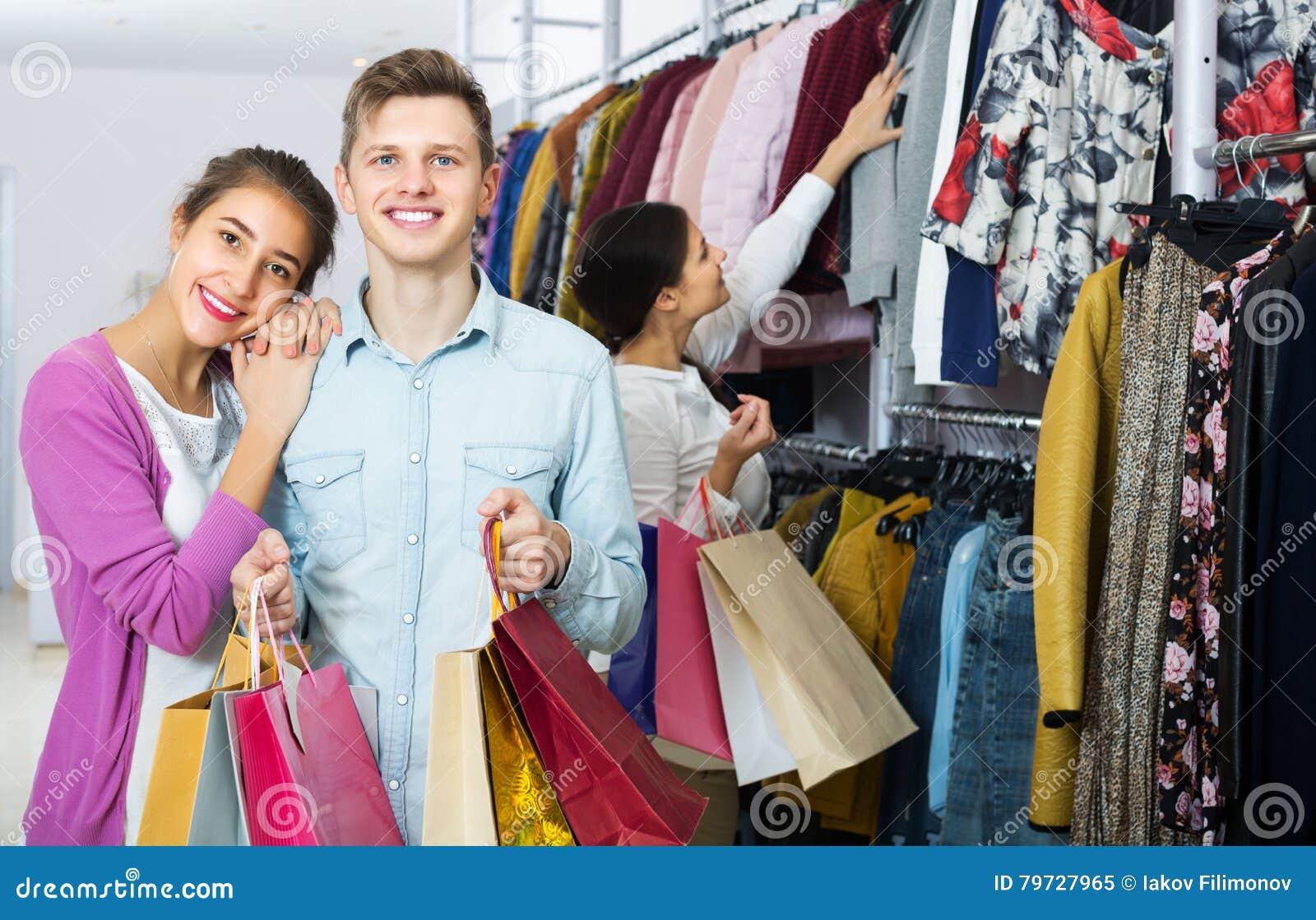 Cónyuges que llevan bolsos en boutique