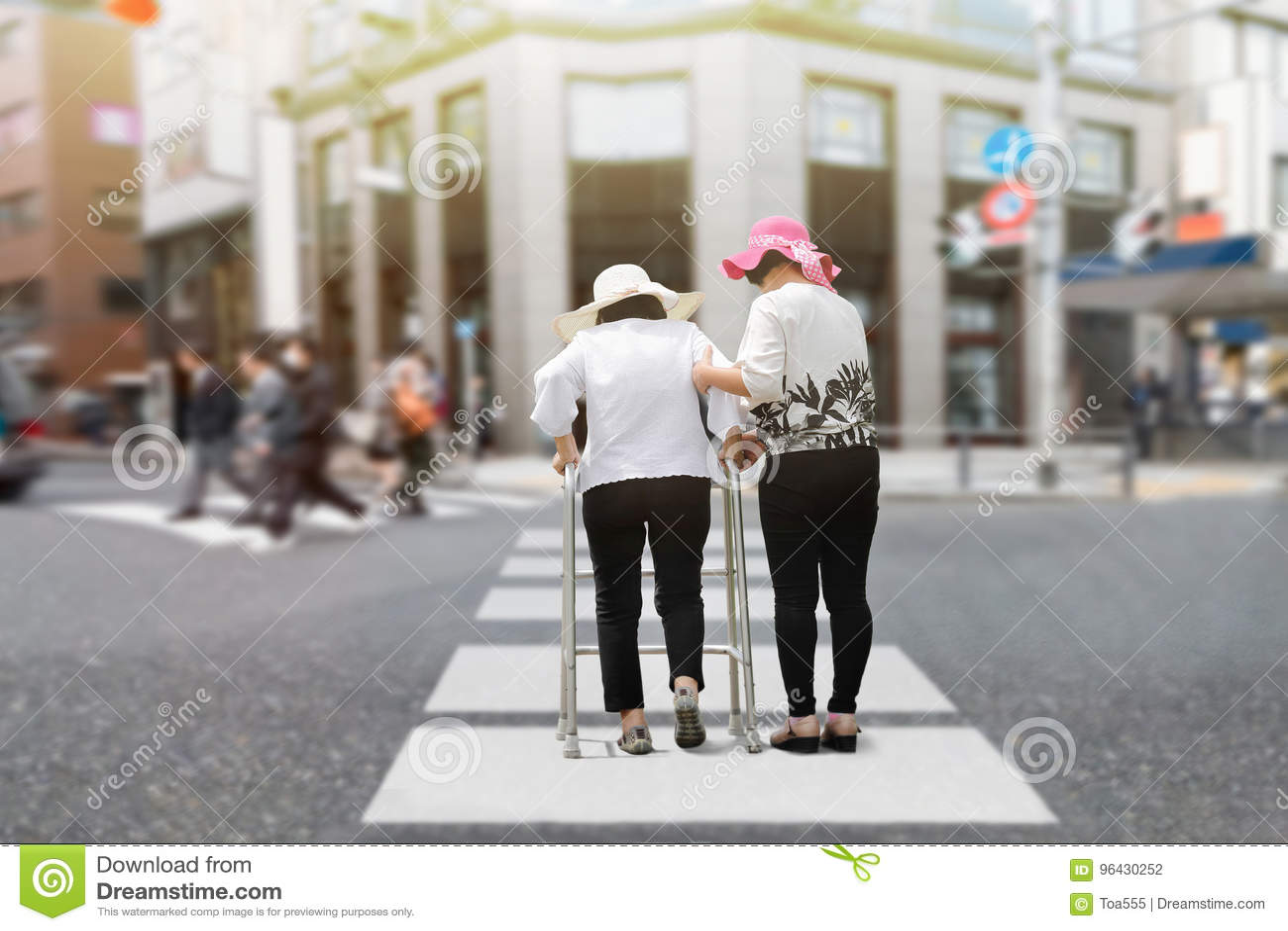 Córka bierze opiece starszego kobiety odprowadzenie przez ulicę