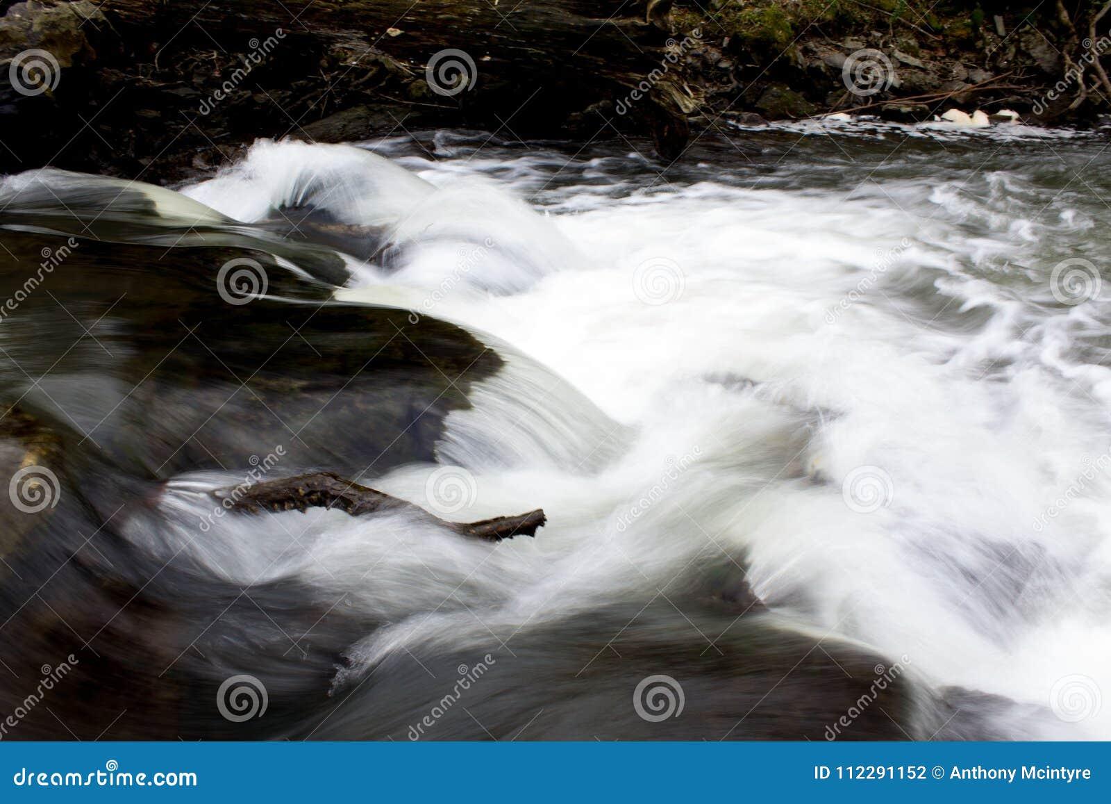Córrego claro branco do rio que apressa-se sobre rochas