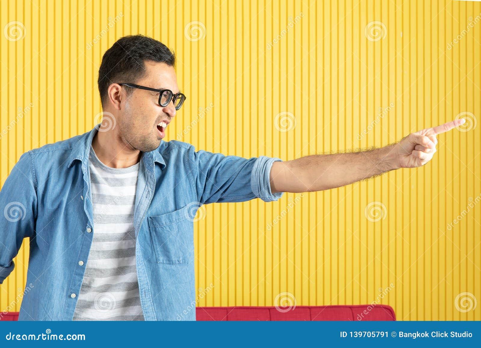 Côté-vue, fin du jeune homme barbu bel asiatique, lunettes de port, dans la chemise de denim, indiquant par espièglerie son côté