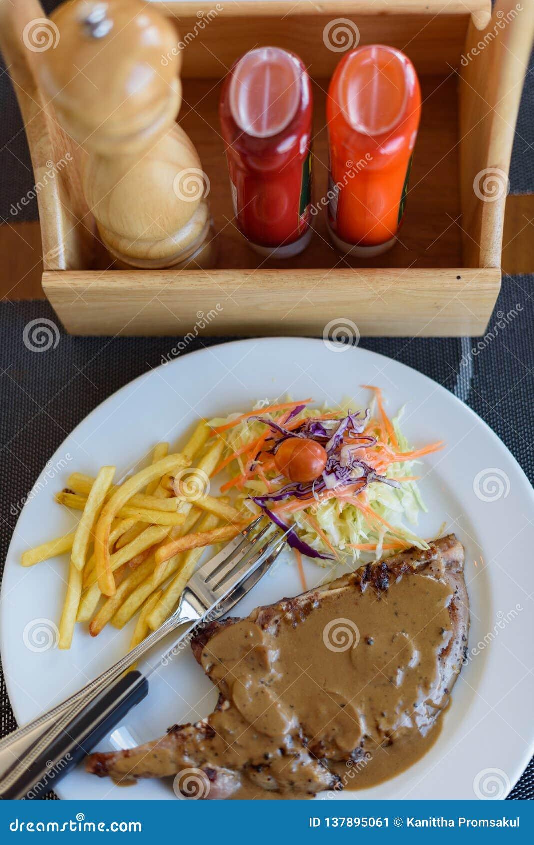 Côtelette de porc grillée avec de la sauce au poivre, les légumes et les pommes frites noirs