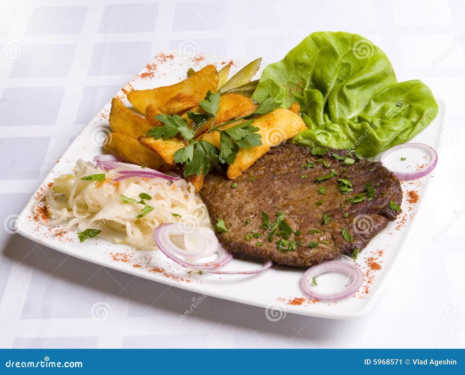 Côtelette de veau avec des lames de salade et de potatoe frit