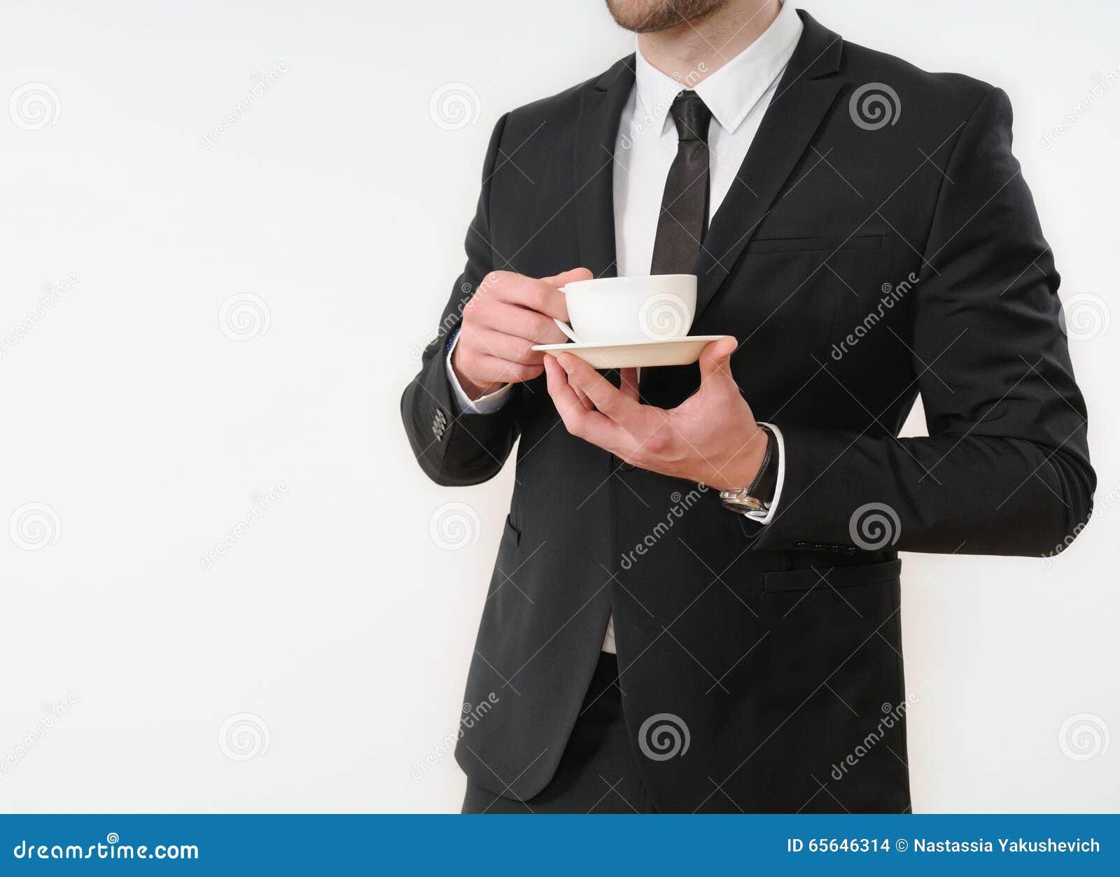 Côté de corps d homme d affaires dans le costume noir avec la tasse de café sur le blanc