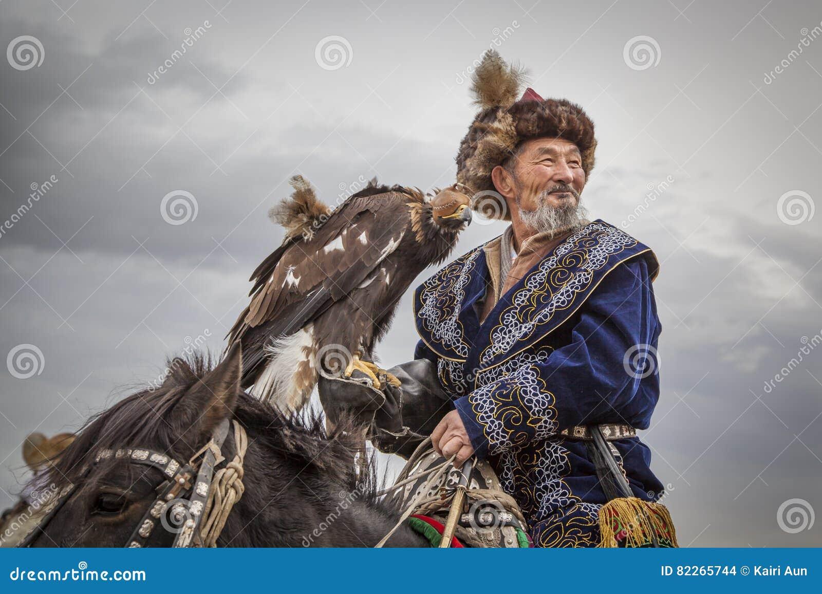 Caçador da águia do nômada do Mongolian em seu cavalo