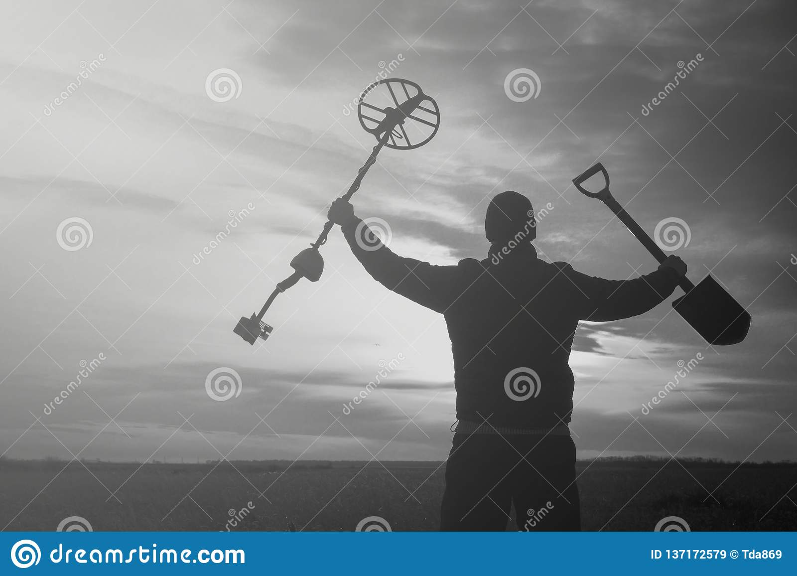 Caçador de tesouro com um detector de metais em um campo de trigo chanfrado à procura da aventura contra o luminoso do sol