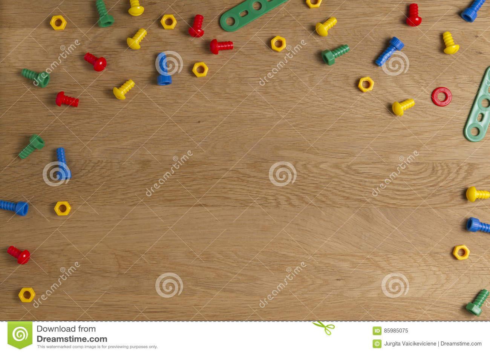 Caçoa a beira das ferramentas dos brinquedos da construção Parafusos e porcas coloridos no fundo de madeira Vista superior Config