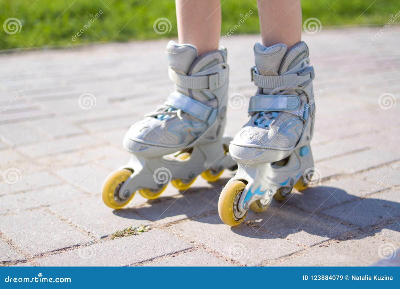 Caçoa os pés em patins de rolo - lazer, infância, jogos exteriores e conceito do esporte