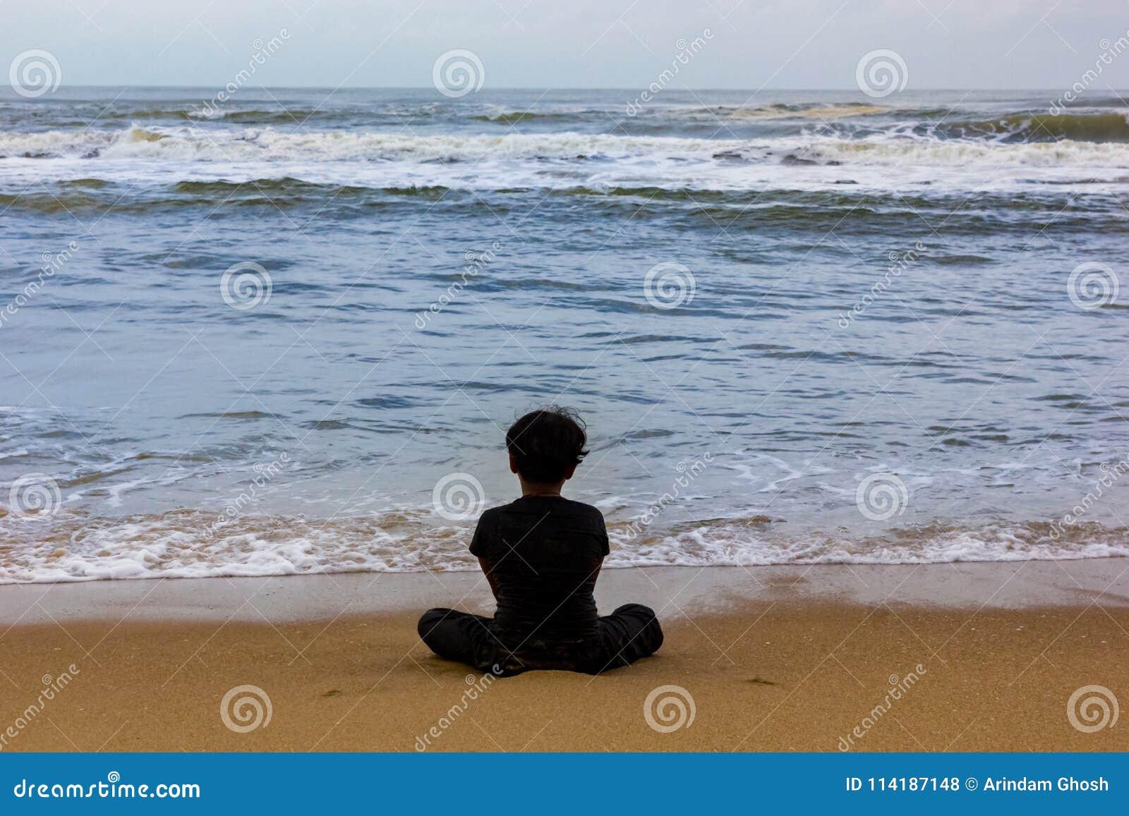 Caçoe o assento isolado em uma opinião da praia de atrás, no conceito da solidão e apenas
