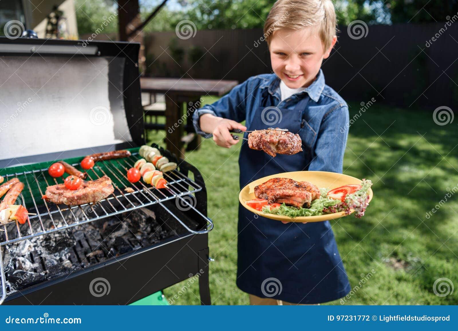 Caçoe o menino no avental que prepara estacas saborosos na grade do assado fora