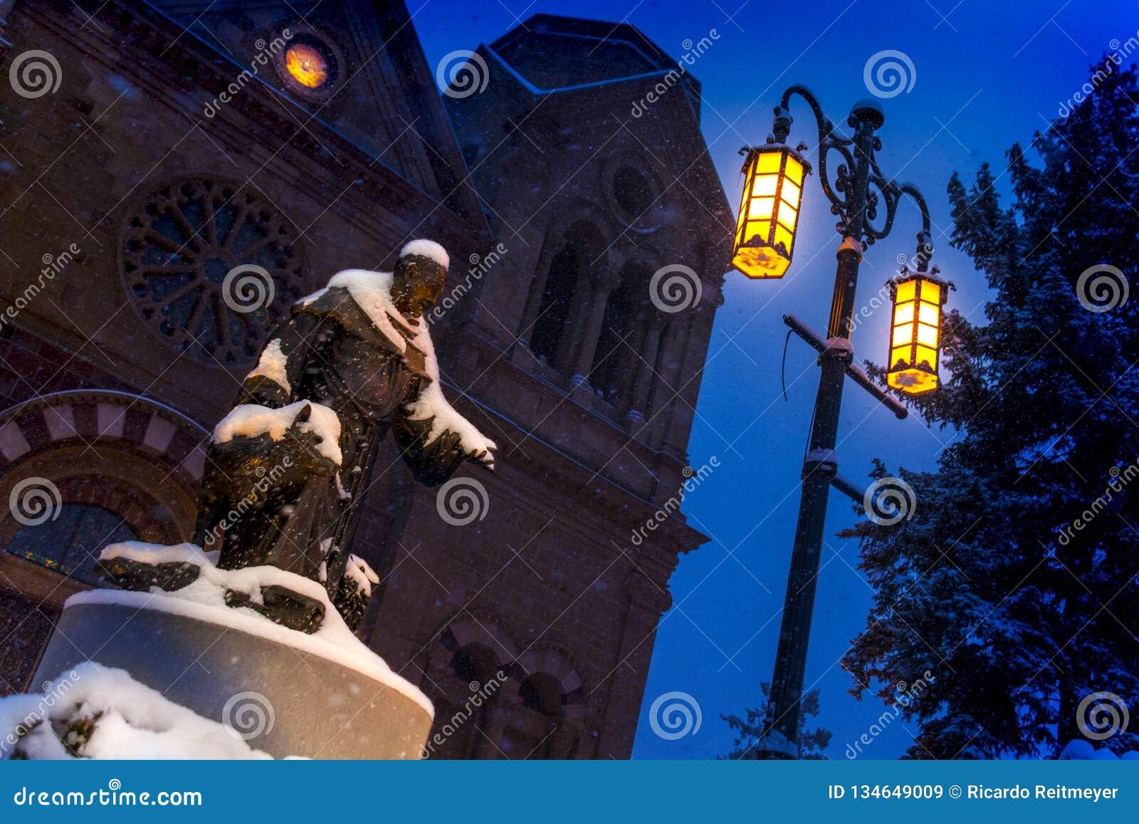 Caídas de la nieve pesadamente en esta escena de la noche de la basílica de St Francis y de St Francis de la estatua de Assisi en