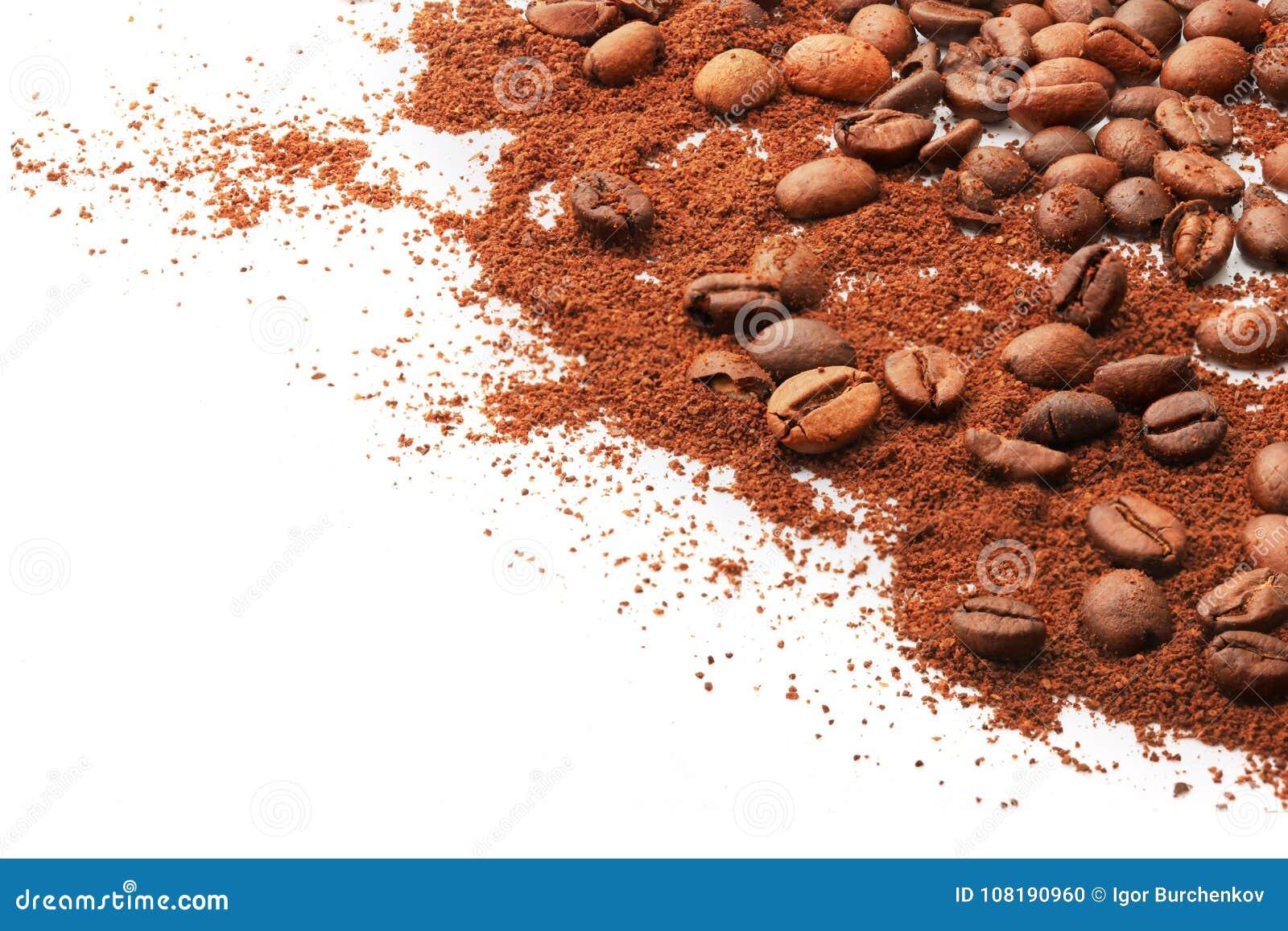 Całe kawowe fasole i ziemia na białym tle