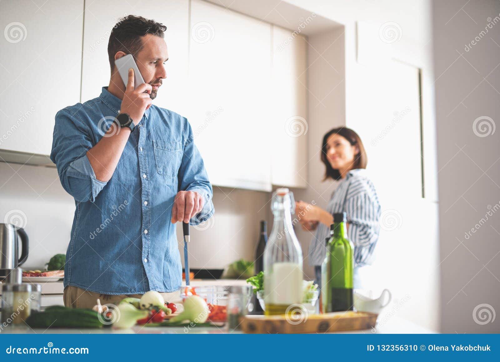 Caballero barbudo hermoso que habla en el teléfono móvil en cocina