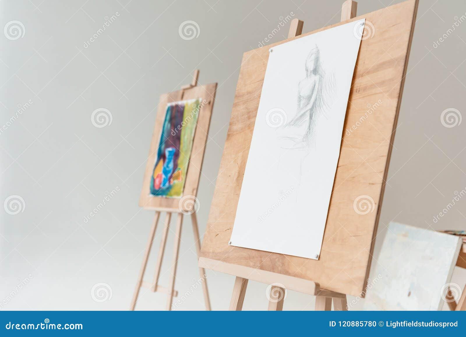 Caballetes con las pinturas artísticas en estudio vacío del arte