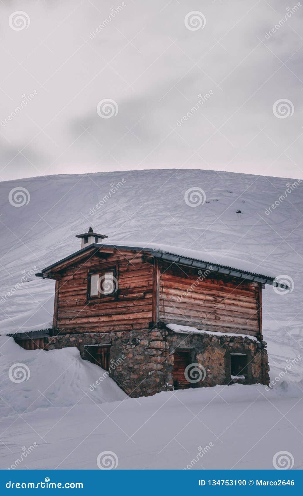 Cabana rústica de madeira de madeira pequena na neve