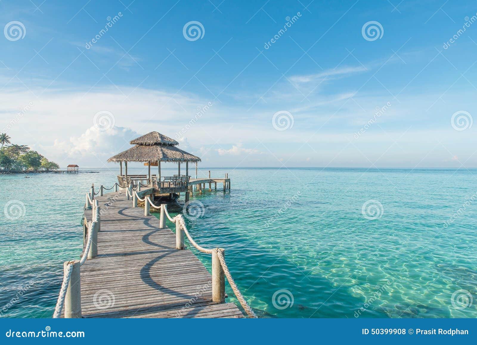 Cabana tropical e ponte de madeira no recurso de feriado Mulher nova na praia do console de Formentera
