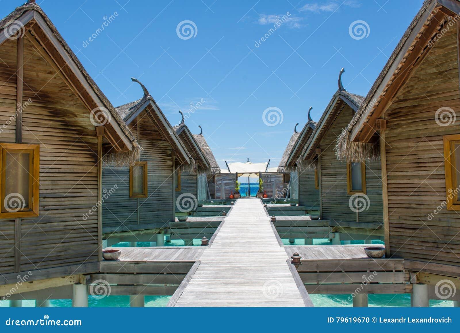 Cabanas na praia tópica em Maldivas