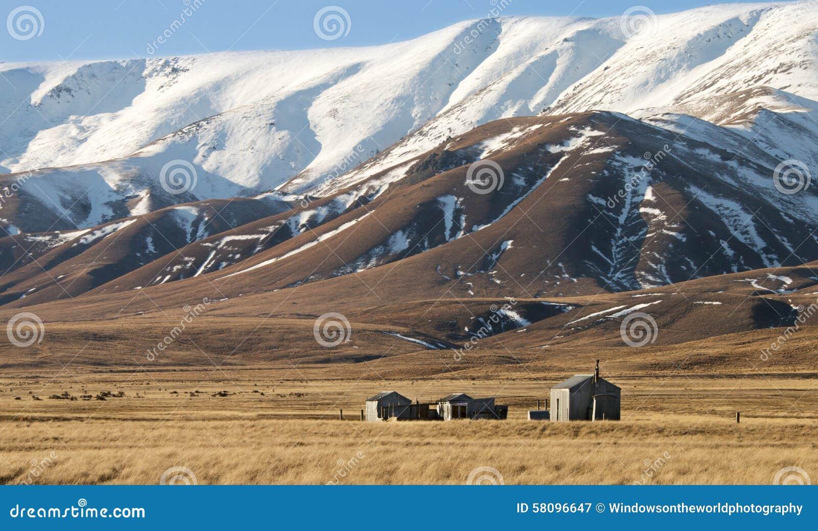 Snowcapped Imágenes De Stock Snowcapped Fotos De Stock: Cabanas Pequenas Em Tussockland Abaixo Das Montanhas