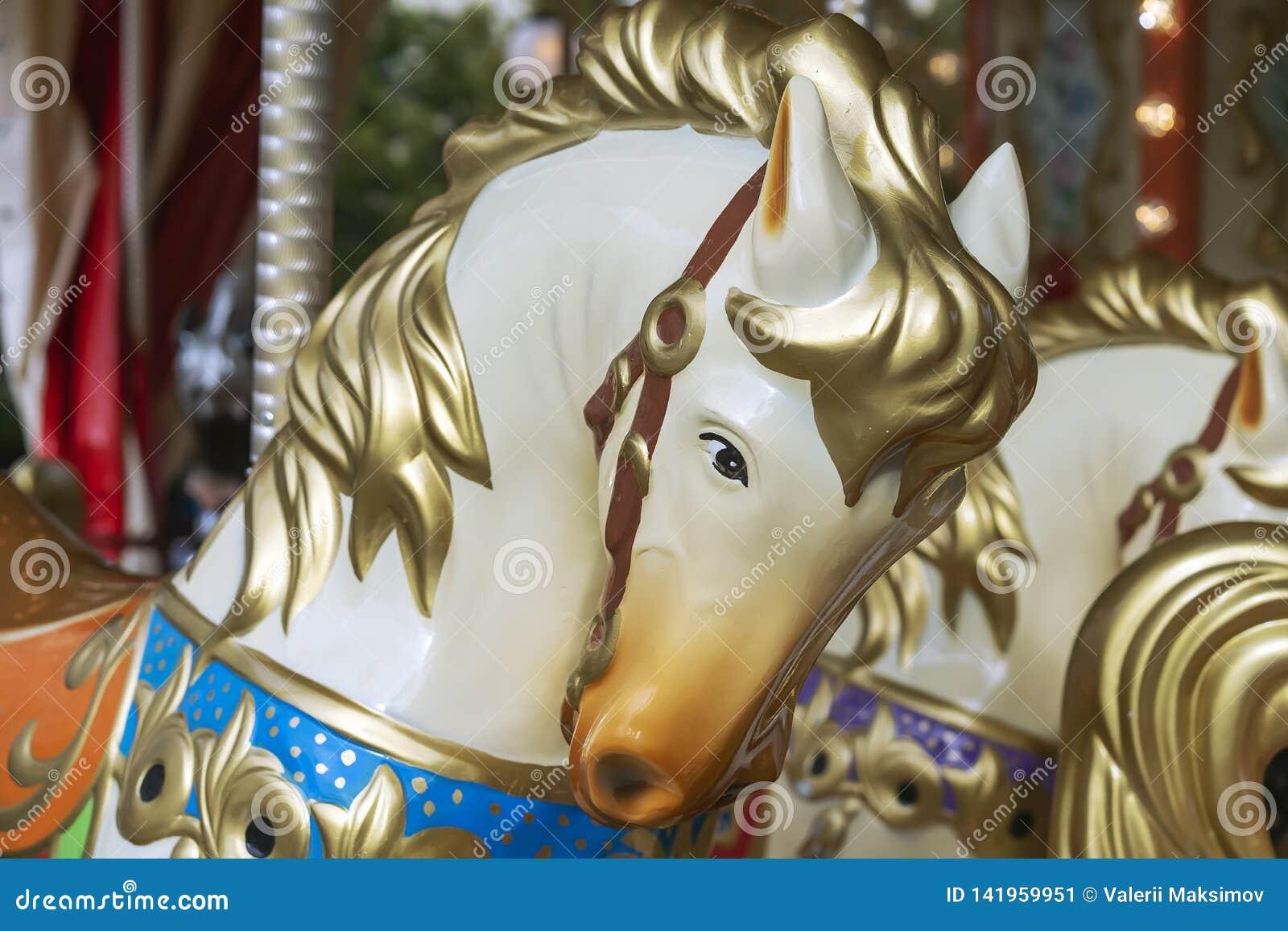 Cabeça de cavalo colorida em um carrossel circular do vintage