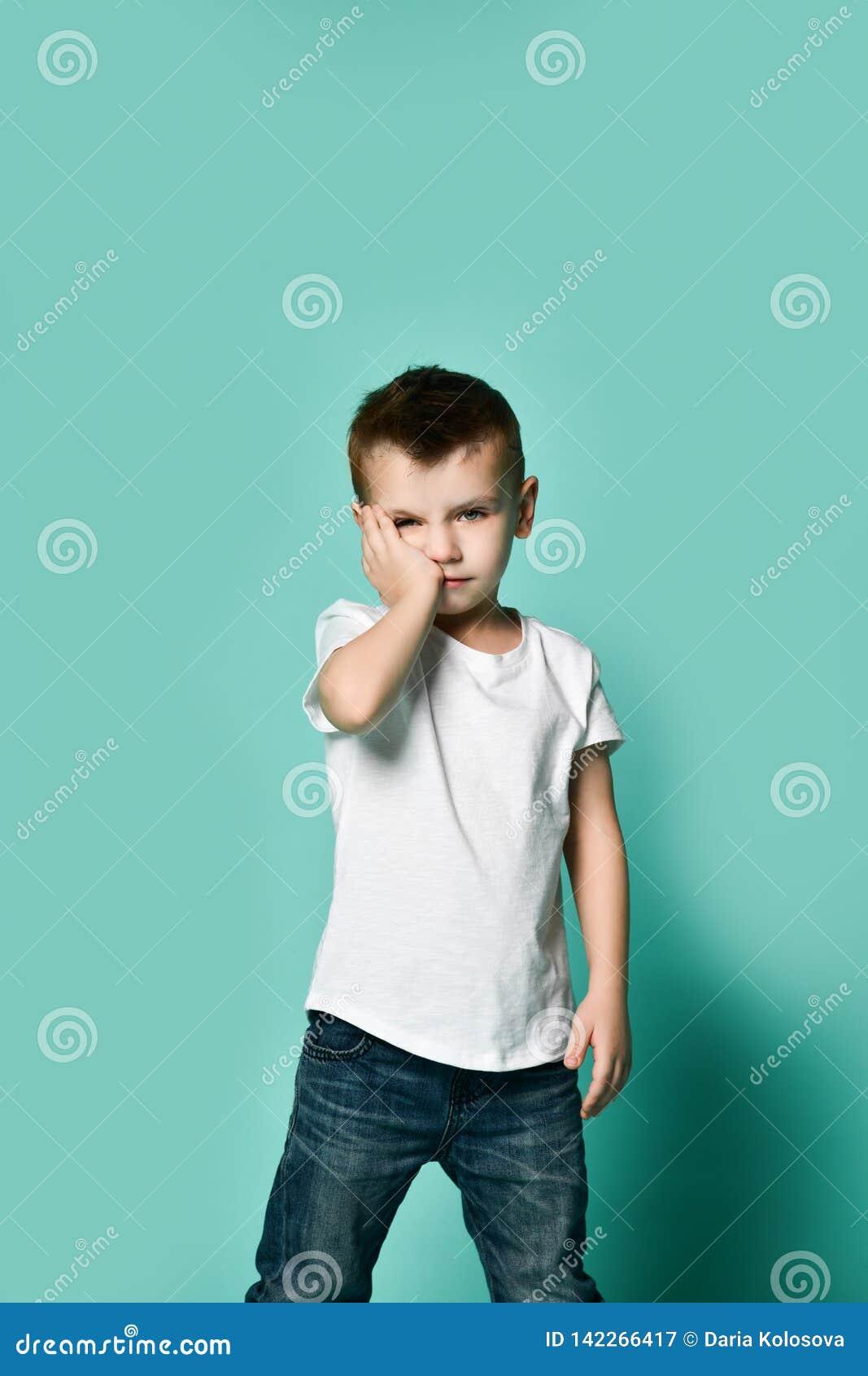Cabeça de inclinação furada triste do menino da criança na palma que olha com olhar indiferente virado no sentimento inquieto, le