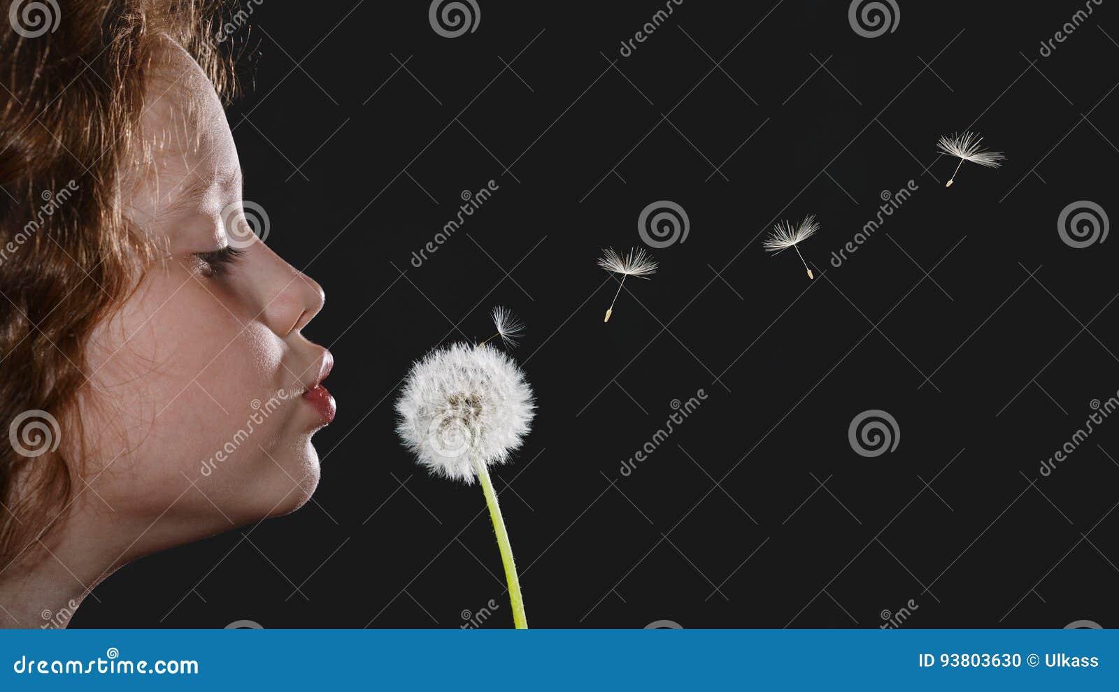 Cabeça de sopro do dente-de-leão da menina do retrato do close up e s de voo