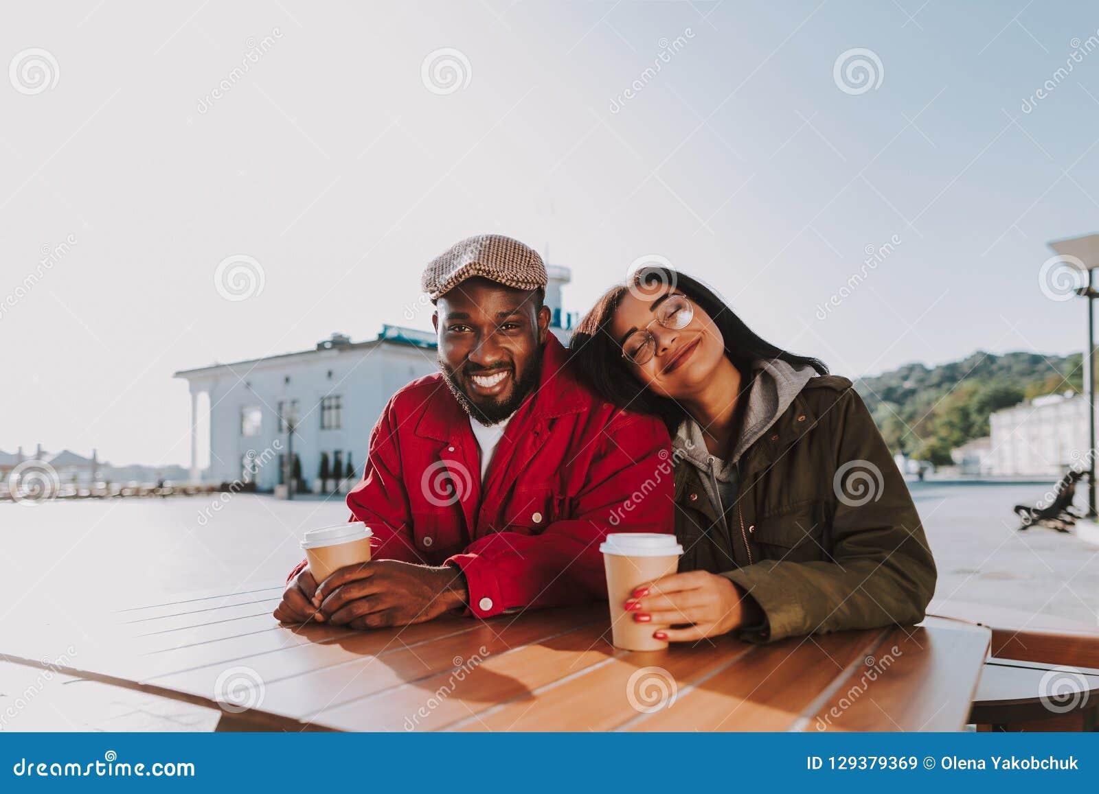 Cabeça de sorriso e de inclinação da mulher feliz no ombro de seu noivo