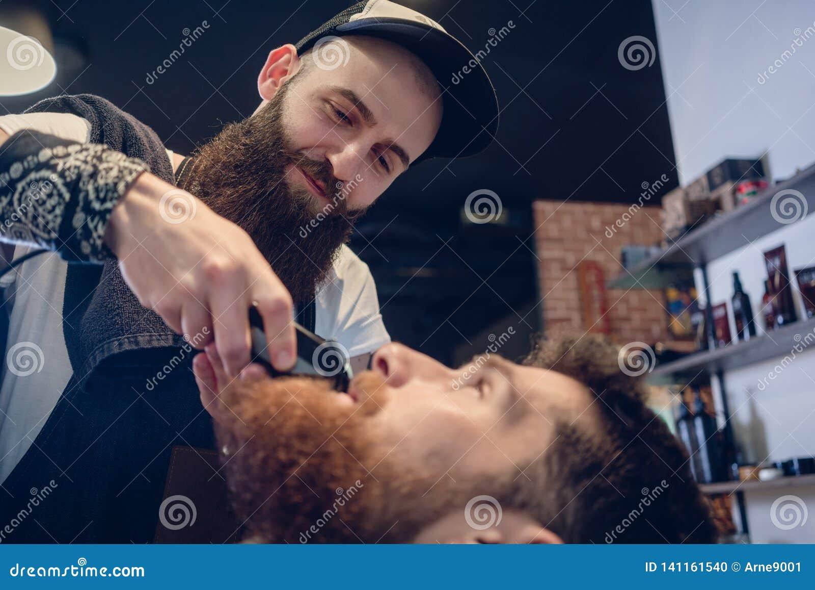 Cabeça de um homem e da mão de um barbeiro que apara sua barba