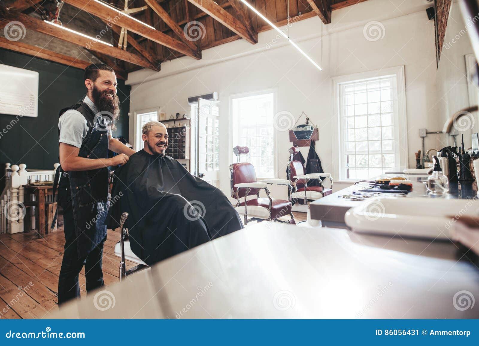 Cabeleireiro com o cliente que senta-se no salão de beleza e no sorriso