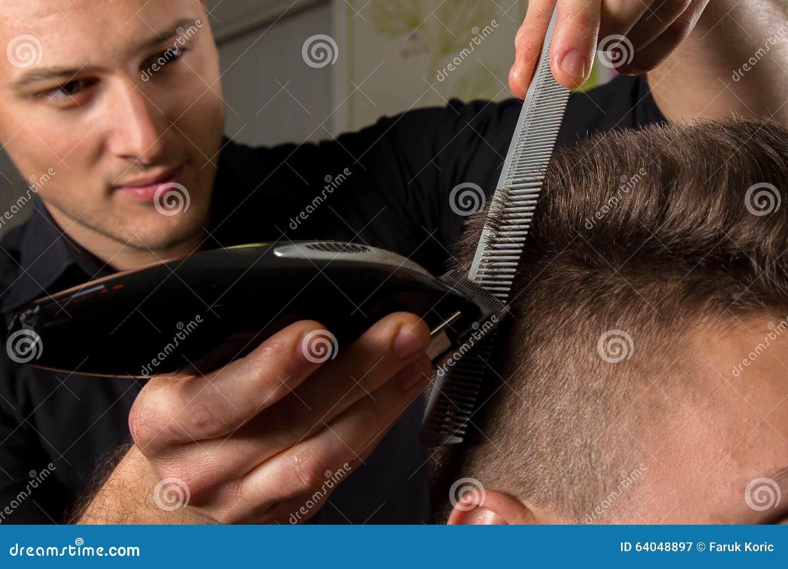 Cabelo dos clientes do corte do cabeleireiro com uma tosquiadeira de cabelo elétrica