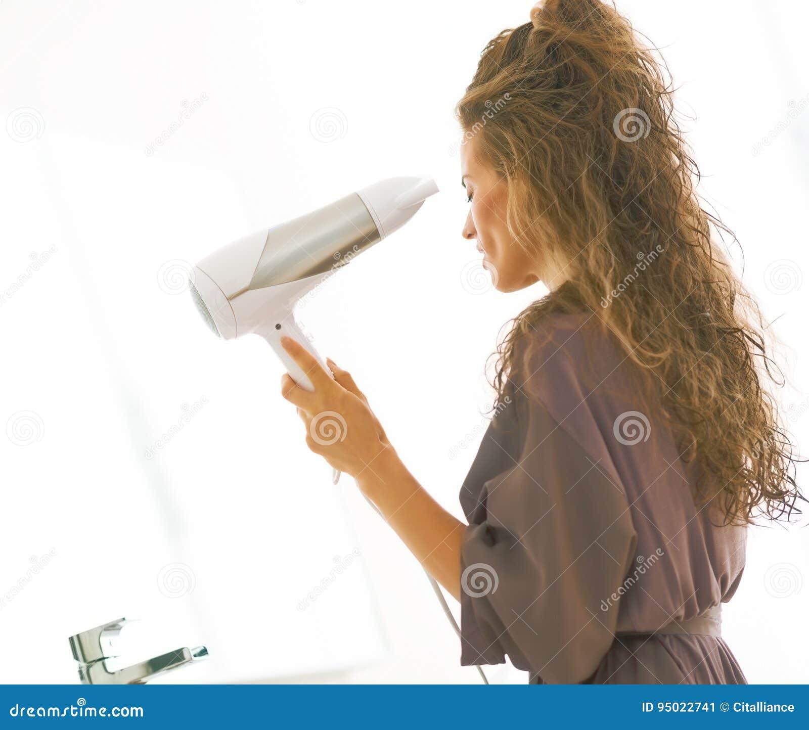 Cabelo secando da jovem mulher no banheiro