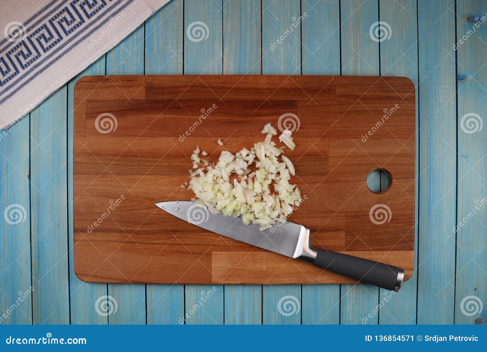 Cabeza de la cebolla negra en un tablero de madera para cortar verduras