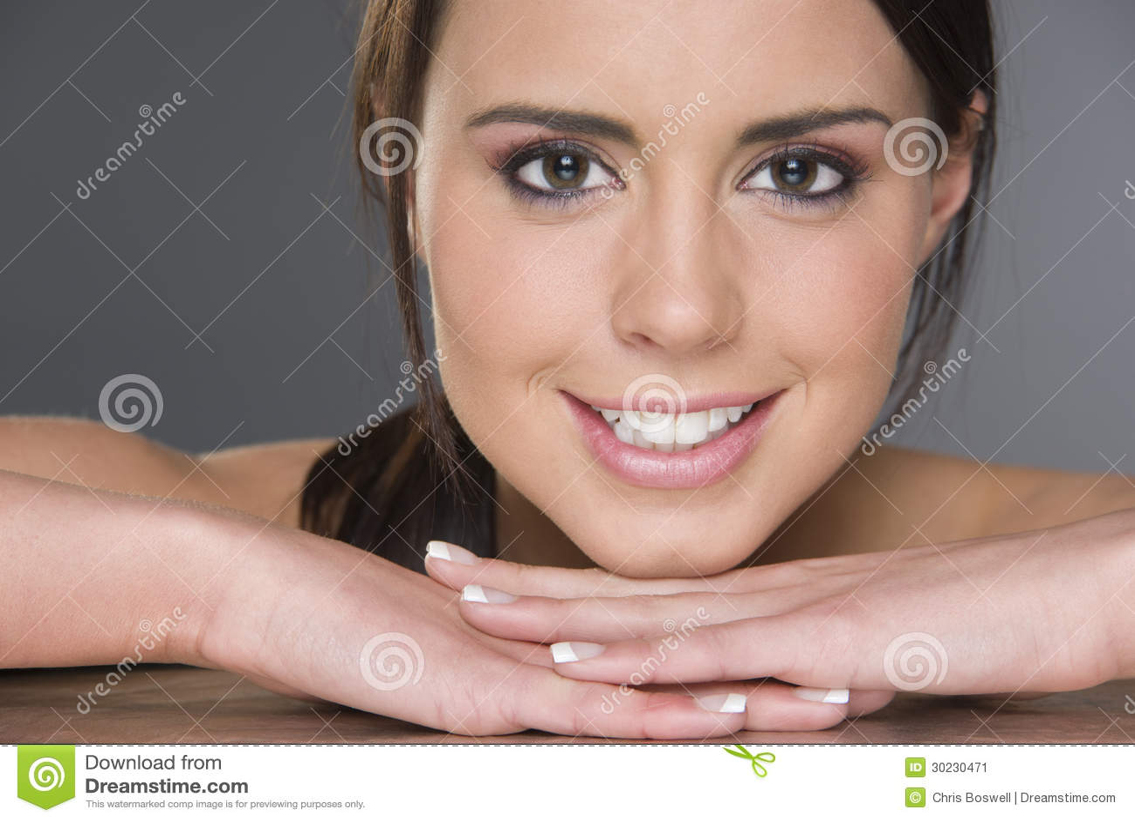 Cabeza de reclinación femenina triguena joven emocionada en Headshot de las manos