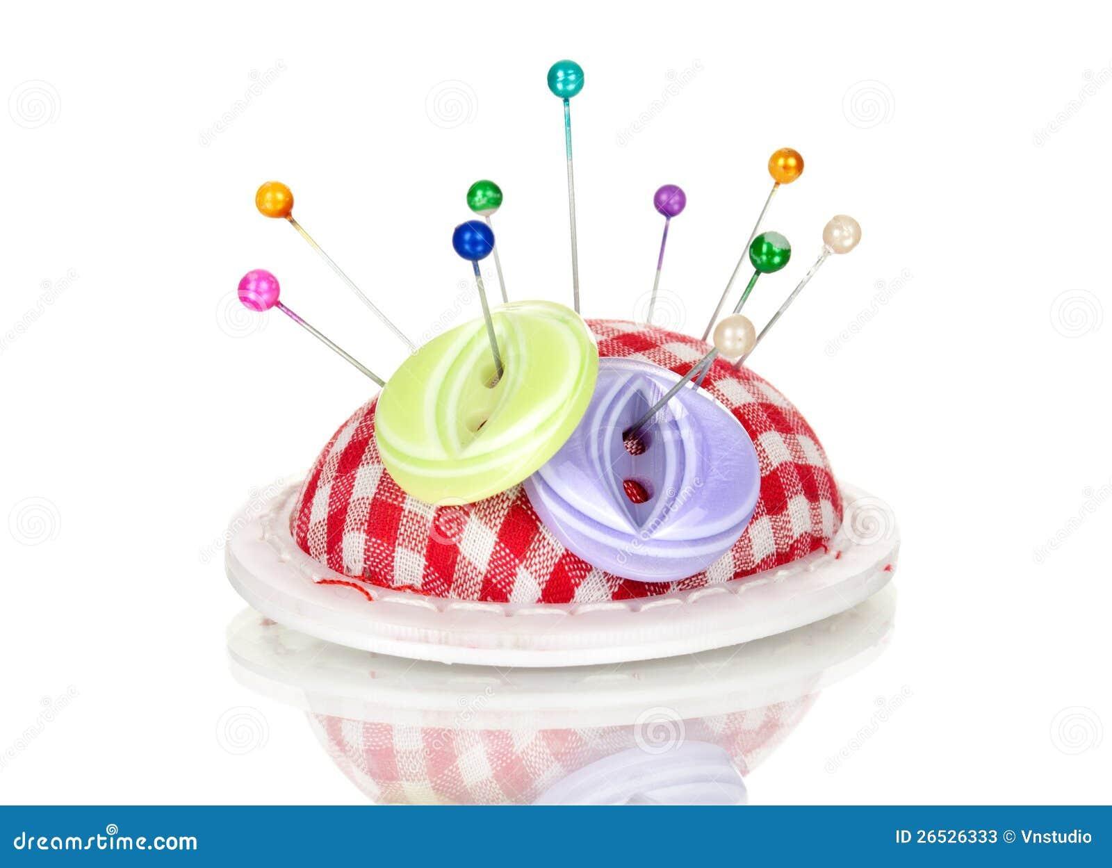 Cabezas de alfiler coloreadas en el acerico y el botón