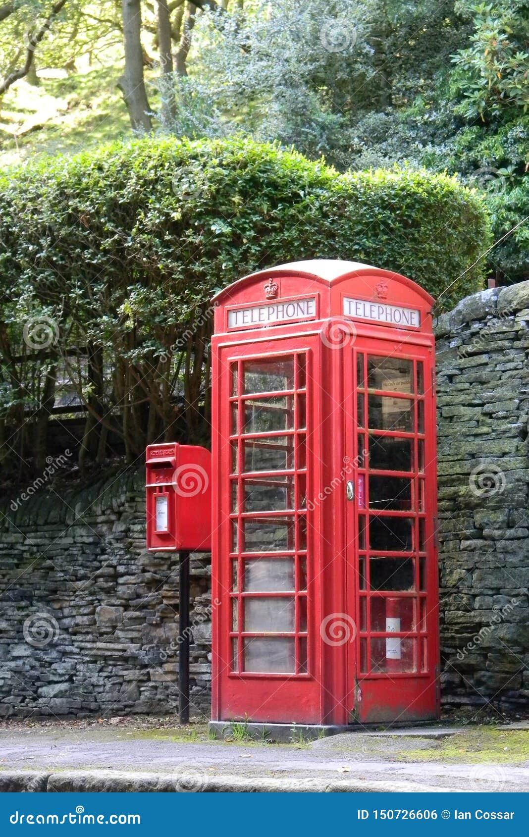 Cabina de teléfonos roja y caja del poste
