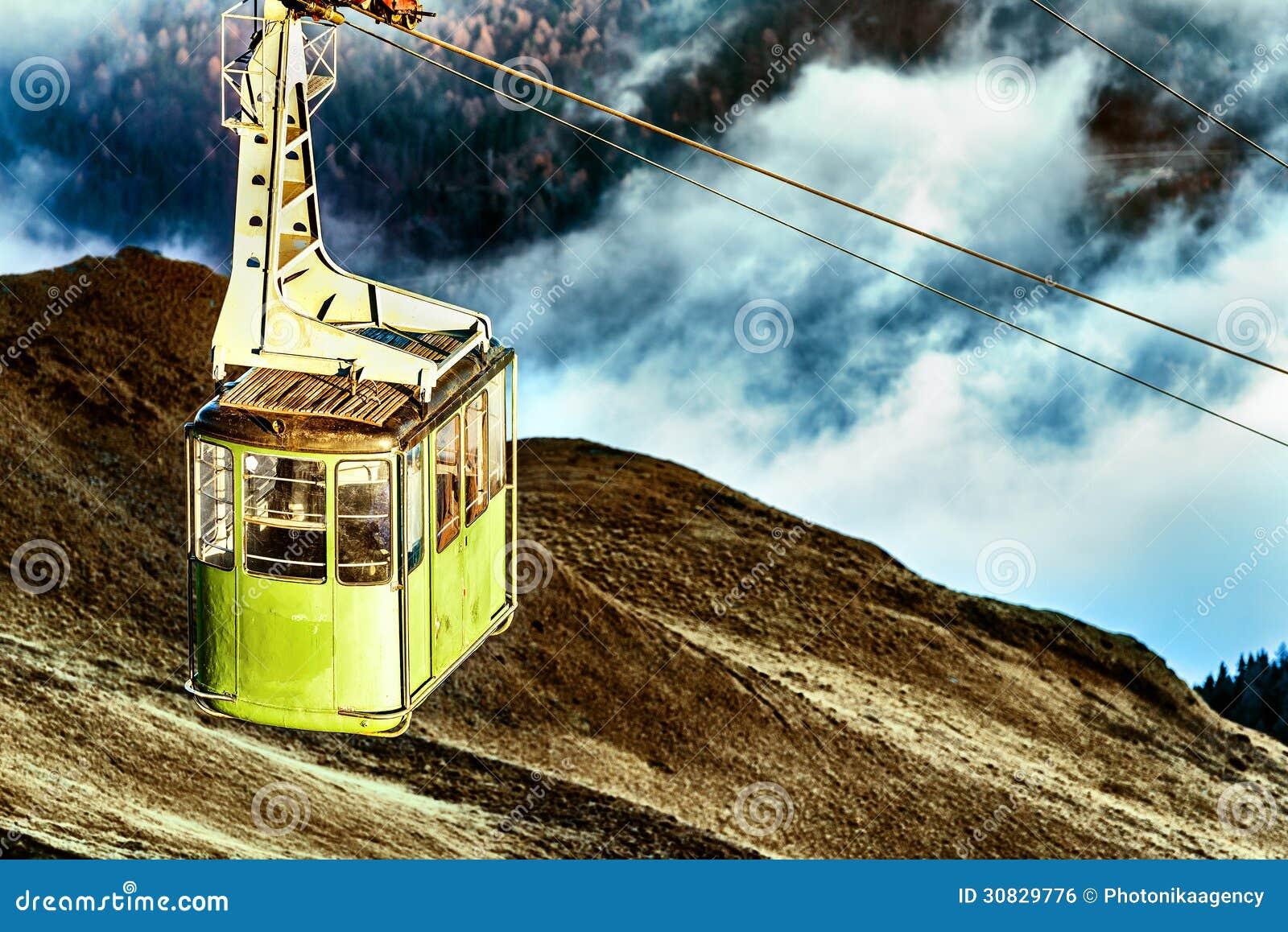 Cabina di funivia che supera sulla montagna e le nuvole