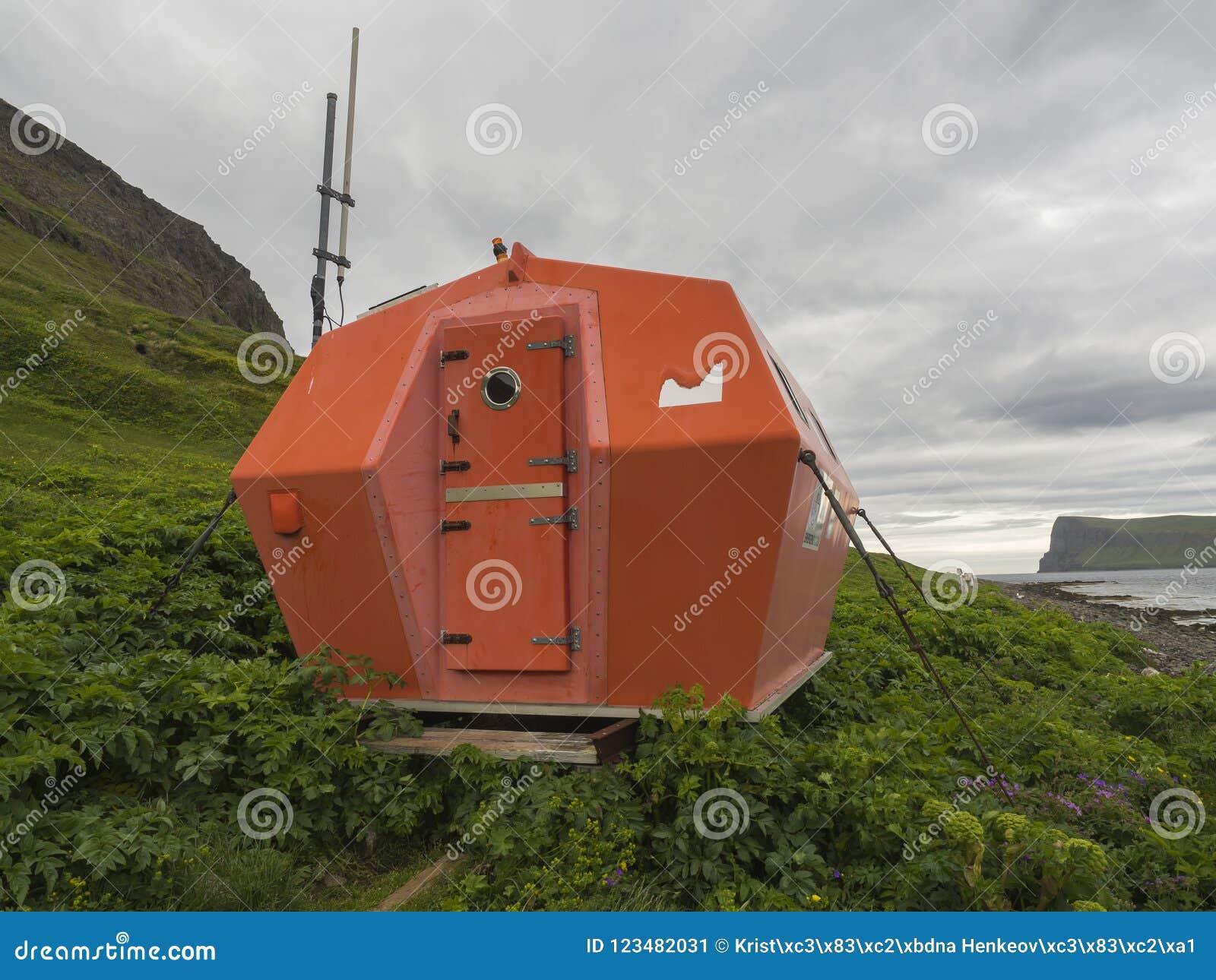 Cabina roja del refugio de la emergencia en Hornvik que se coloca en el prado de la hierba de la orilla de mar con la opinión sob