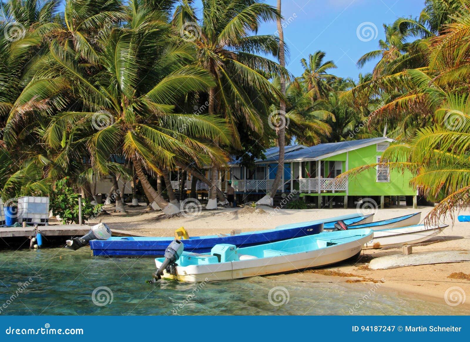 Cabinas en los zancos en la pequeña isla del tabaco Caye, Belice