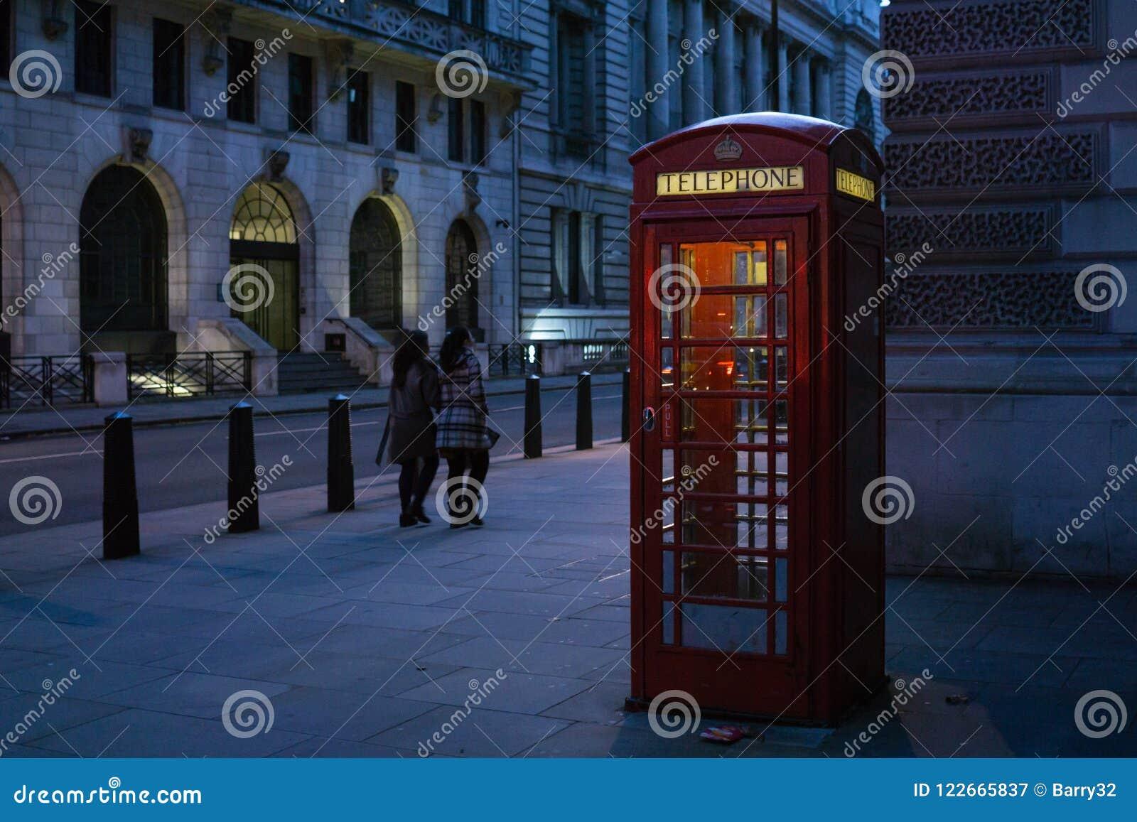 Cabine téléphonique rouge britannique traditionnelle sur la rue de Londres, illuminée de dans le côté la nuit