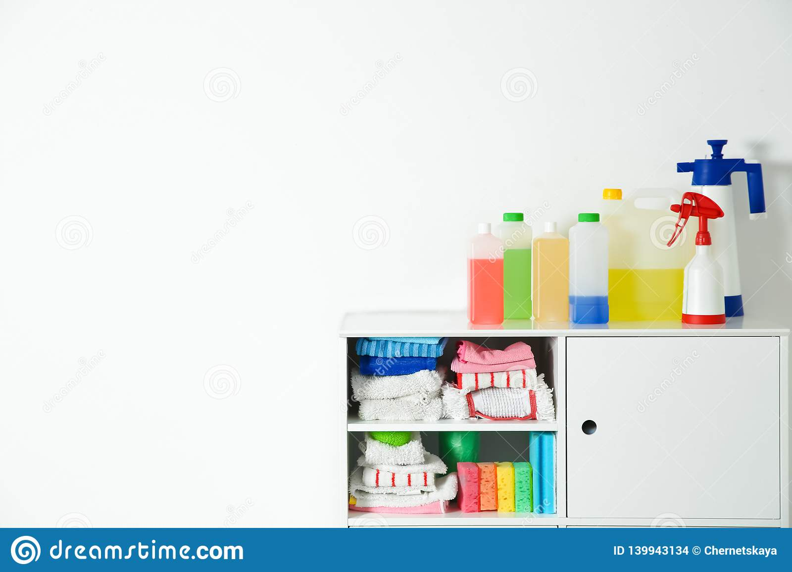 Cabinet With Different Cleaning Supplies On White Background