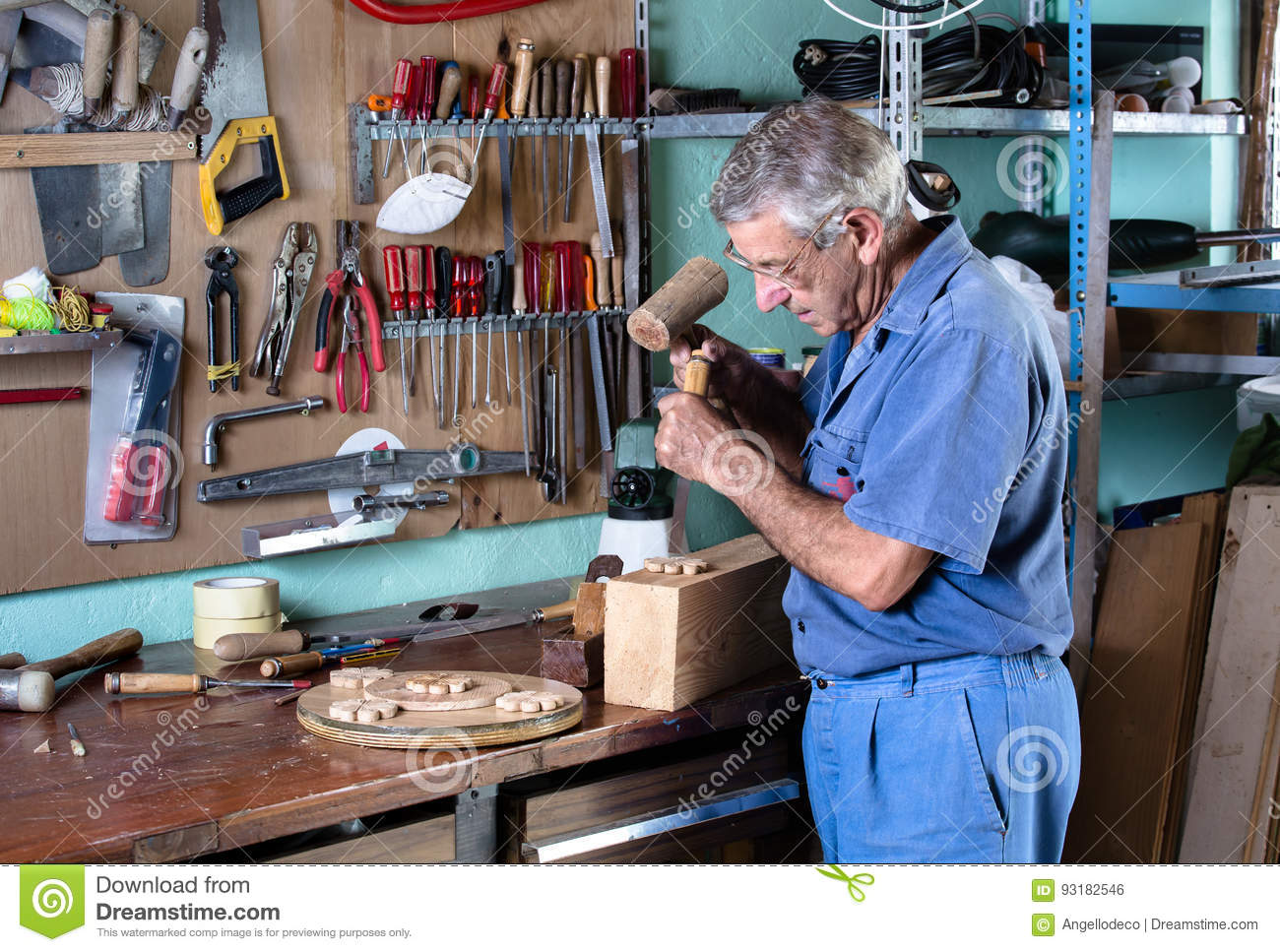 Cabinetmaker carving wood with a chisel and hammer in workbench
