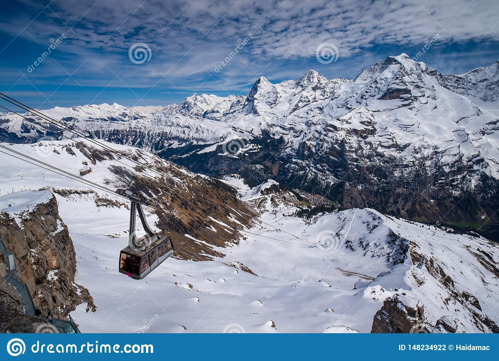 Cable car against breathtaking panoramic view of famous peaks Eiger, Monch and Jungfrau in Swiss Alps, Switzerland