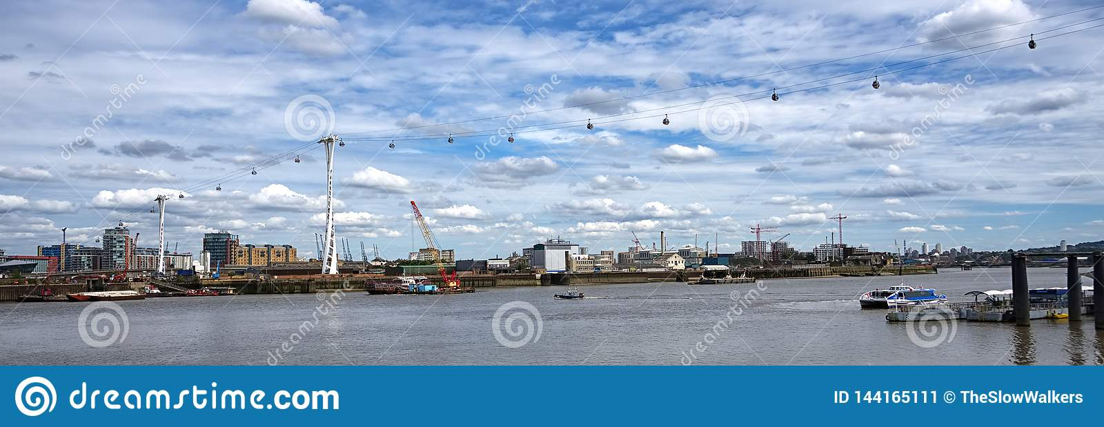 Wide angle. Cable cars crossing over River Thames, London.