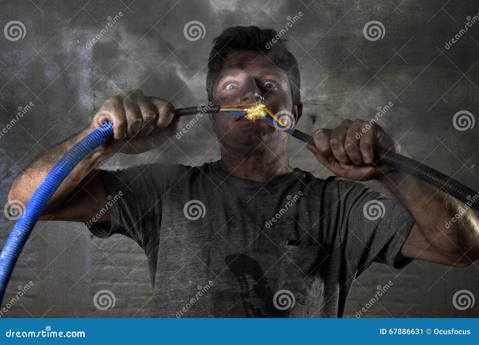 Cable que se une a del hombre inexperimentado que sufre accidente eléctrico con la expresión quemada sucia del choque de la cara