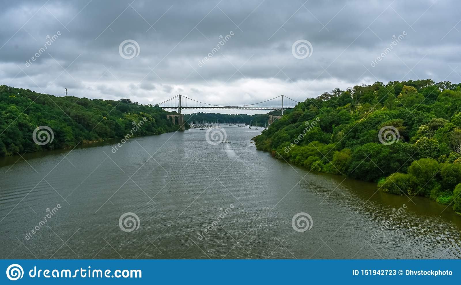 Cable-stayed bridge in a green natural forest, with a dramatic cloudy sky. Motorboat sailing on the river