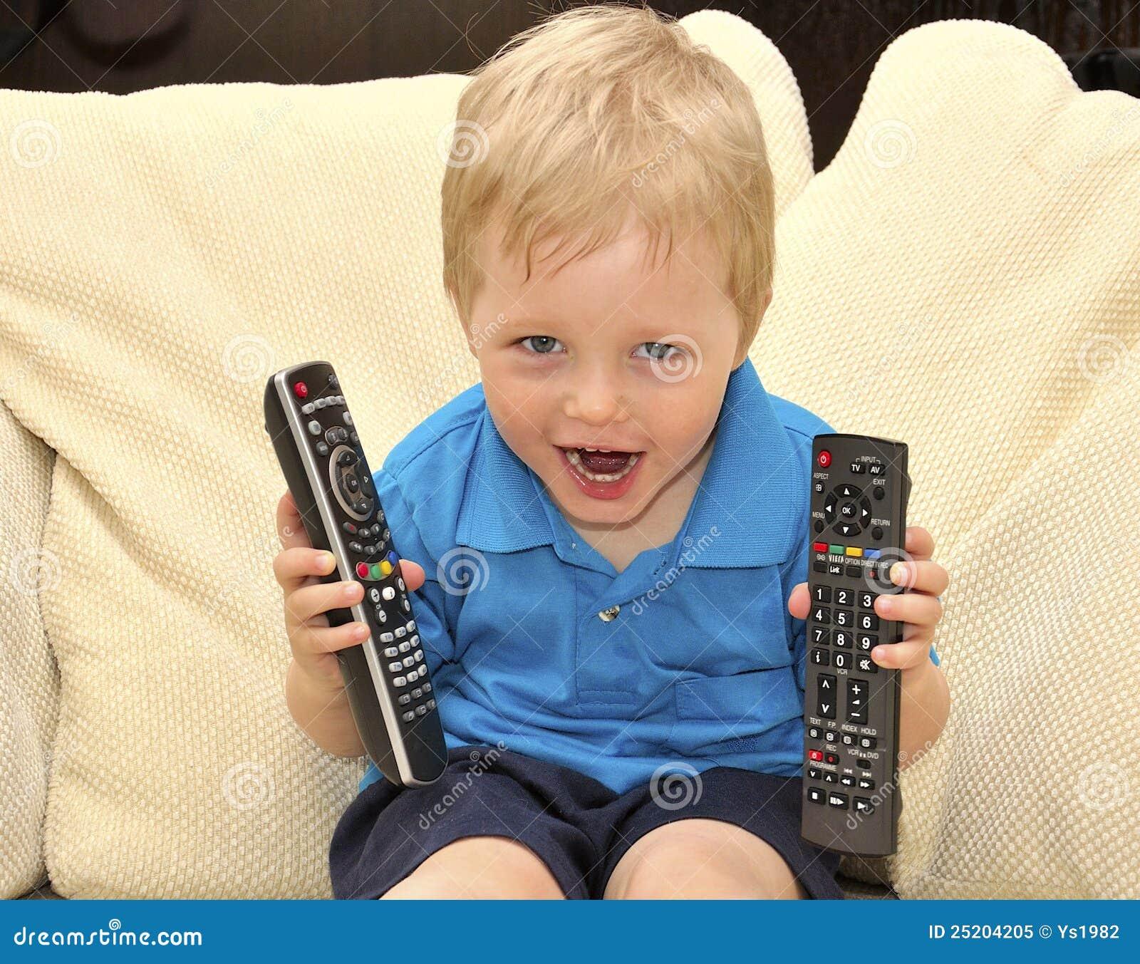 Cabrito lindo que ve la TV, sentándose en silla