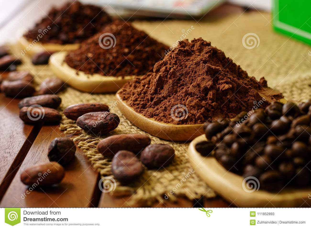 Cacao powder, cocoa nibs, and coffee beans on wooden plates on burlap