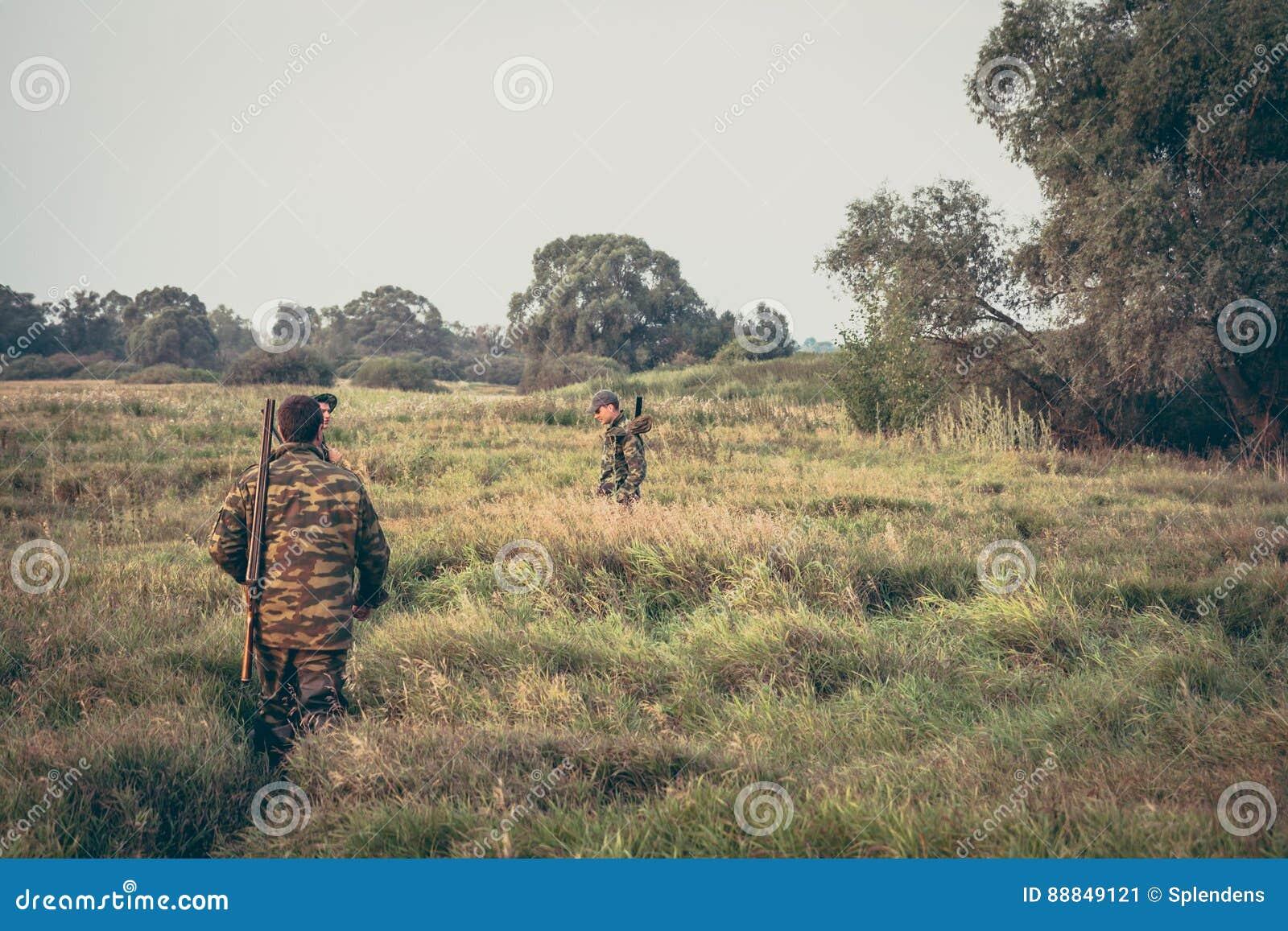 Cacciatori che attraversano attraverso l erba alta nel campo rurale durante la stagione di caccia