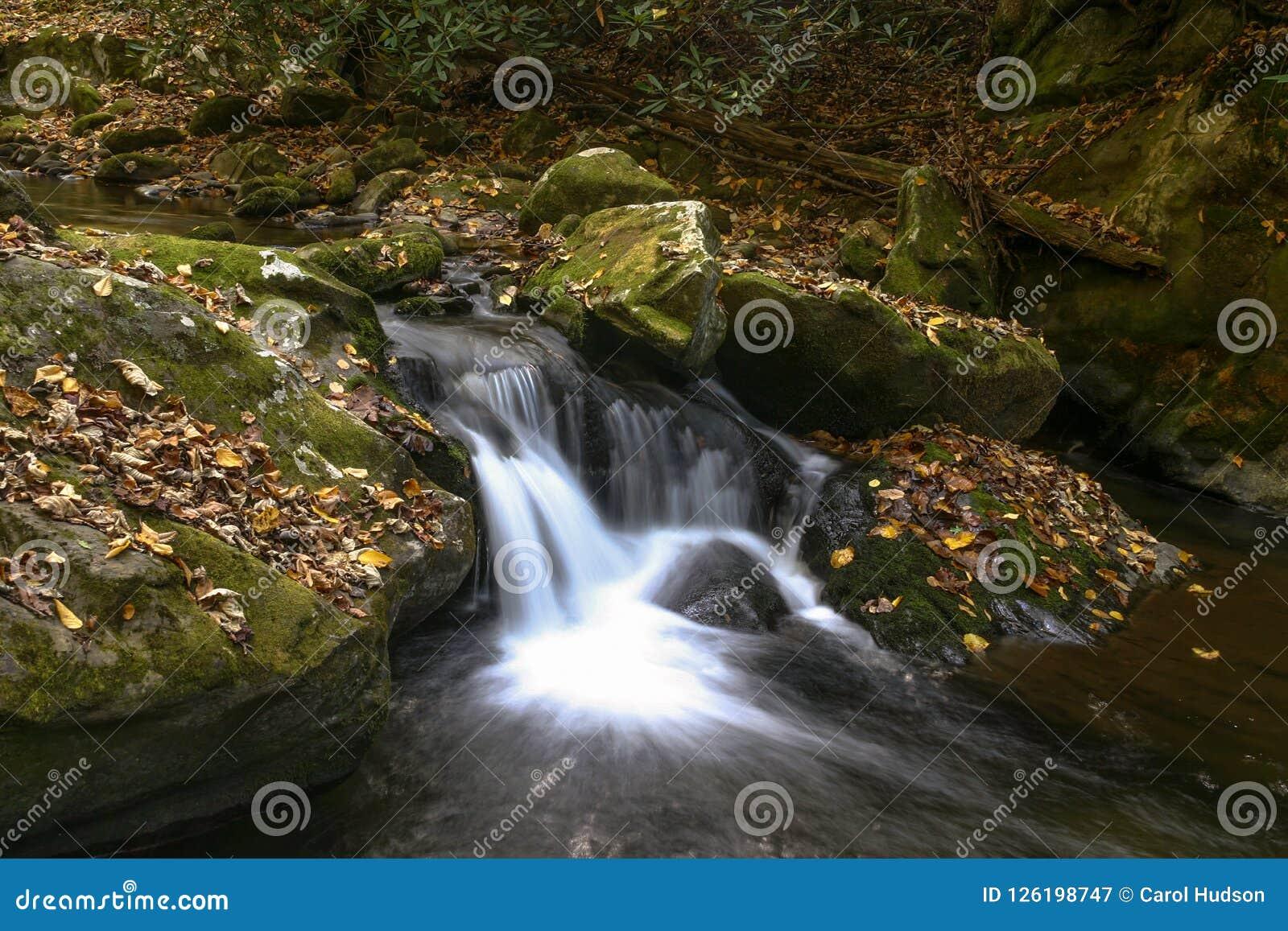 Cachoeira ao longo do córrego nas montanhas fumarentos na queda