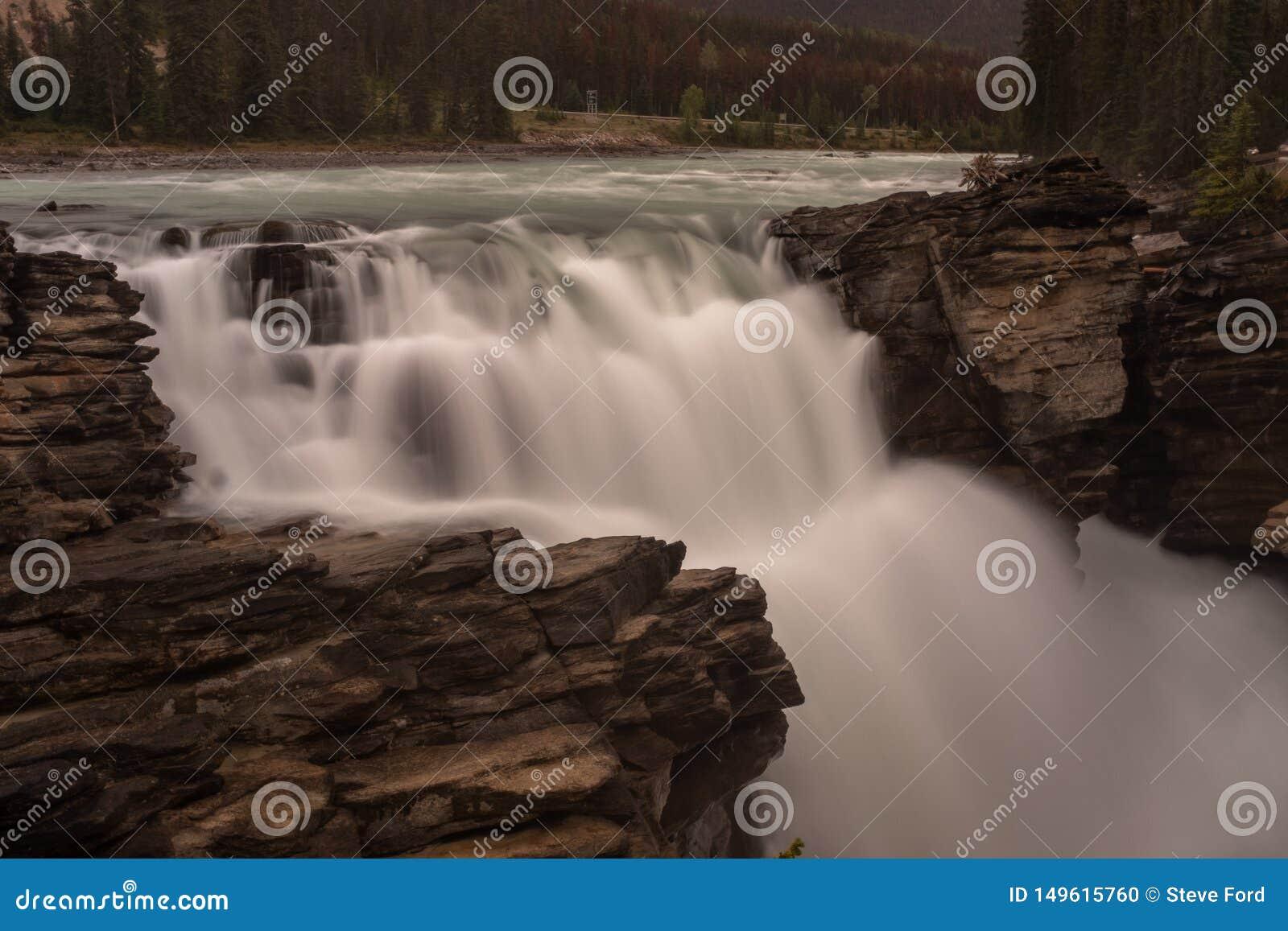 A cachoeira poderosa de Athabasca no parque nacional de Banff, Canadá, a torrente de apertos da água com uma diferença nas rochas